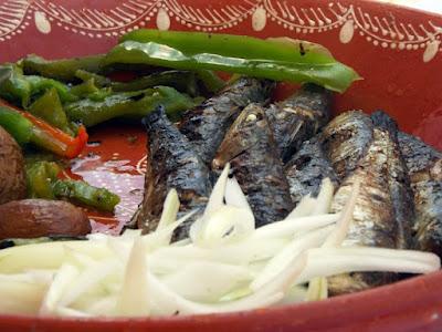 Travessa com sardinhas assadas, cebolas, batatas ao murro e pimentos assados.
