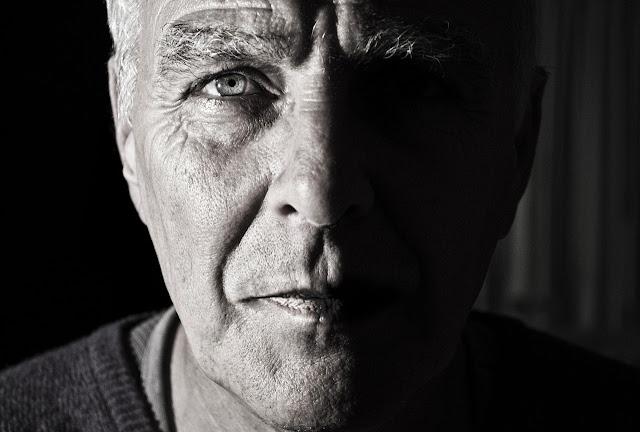 foto preto e branco rosto homem idoso luz nos olhos e restante em sombra