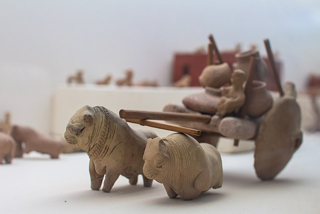 An Indus Valley Civilization toy Bull Cart with human figurine and vessels made from terracotta
