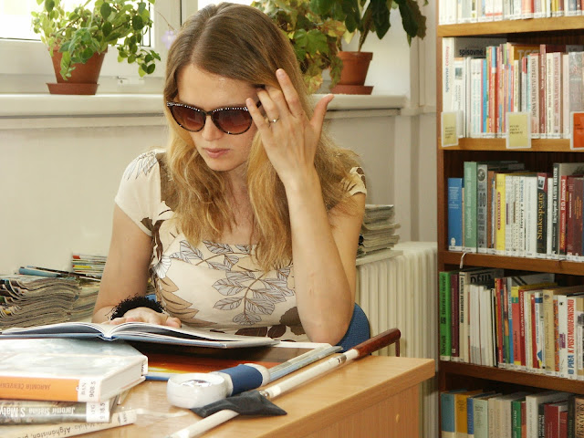 Linda sedí u stolu v knihovně a studuje knihu