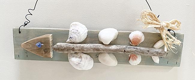 driftwood, shells and raffia on a board shaped like a fish