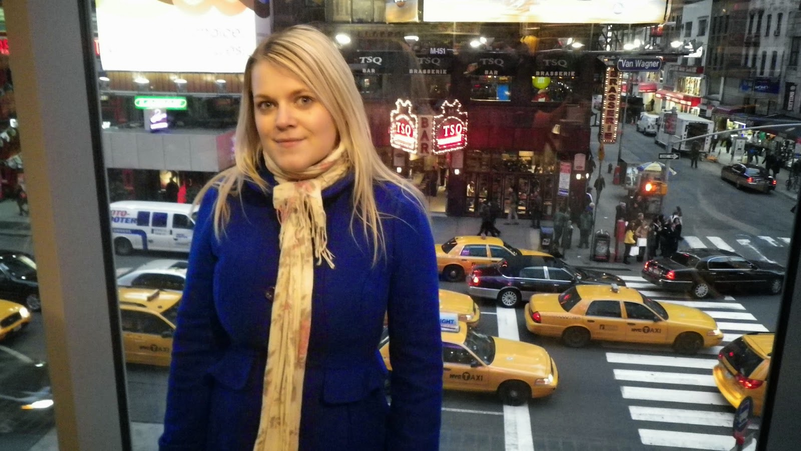 girl in blue coat in front of yellow cabs in New York