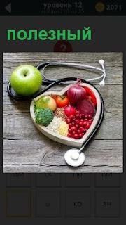 На деревянной поверхности лежат полезные фрукты и овощи в виде изображения сердца, а вокруг них стетоскоп