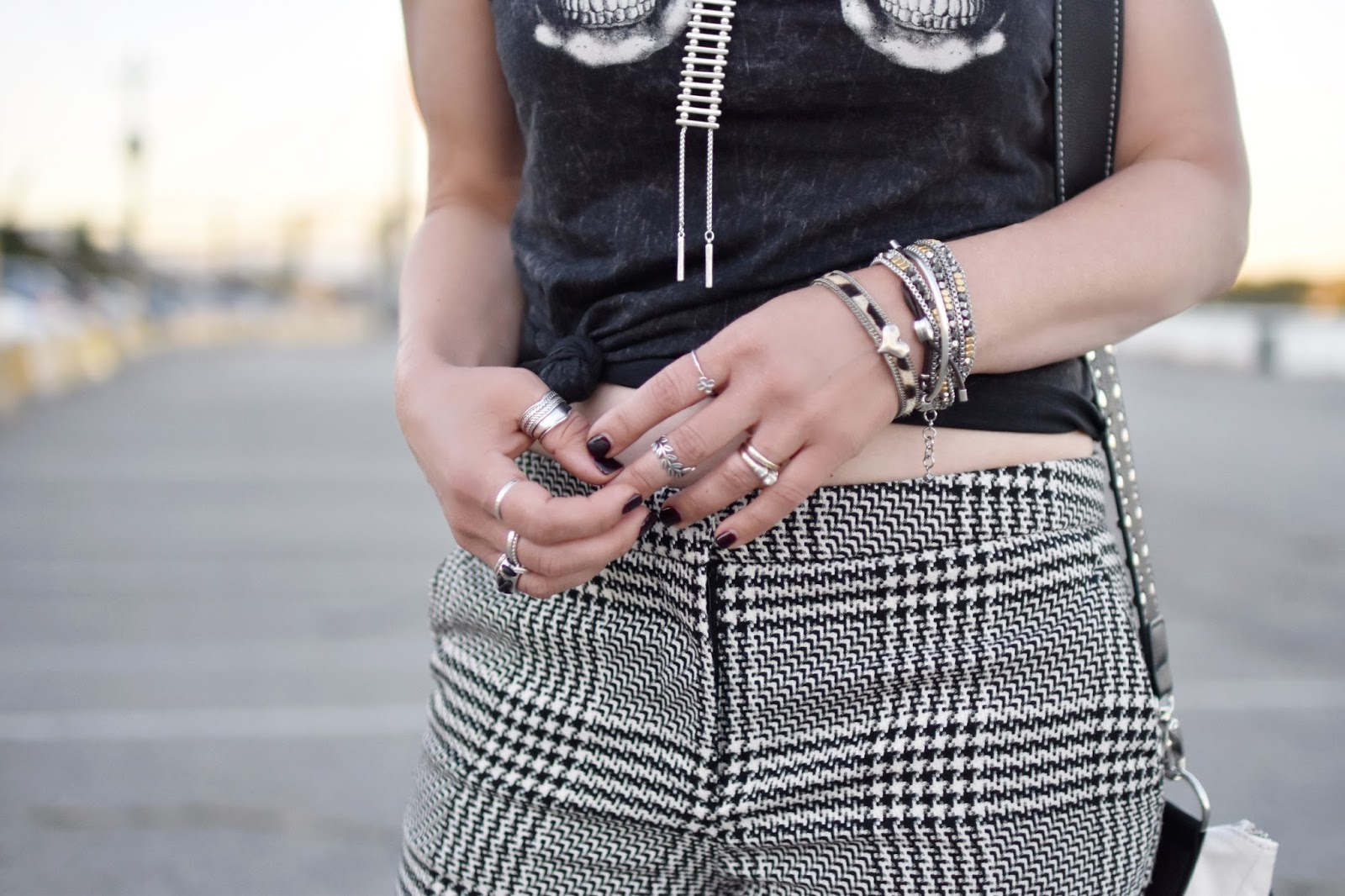 Monika Faulkner outfit inspiration - houndstooth trousers, skull-patterned tee, layered bracelets