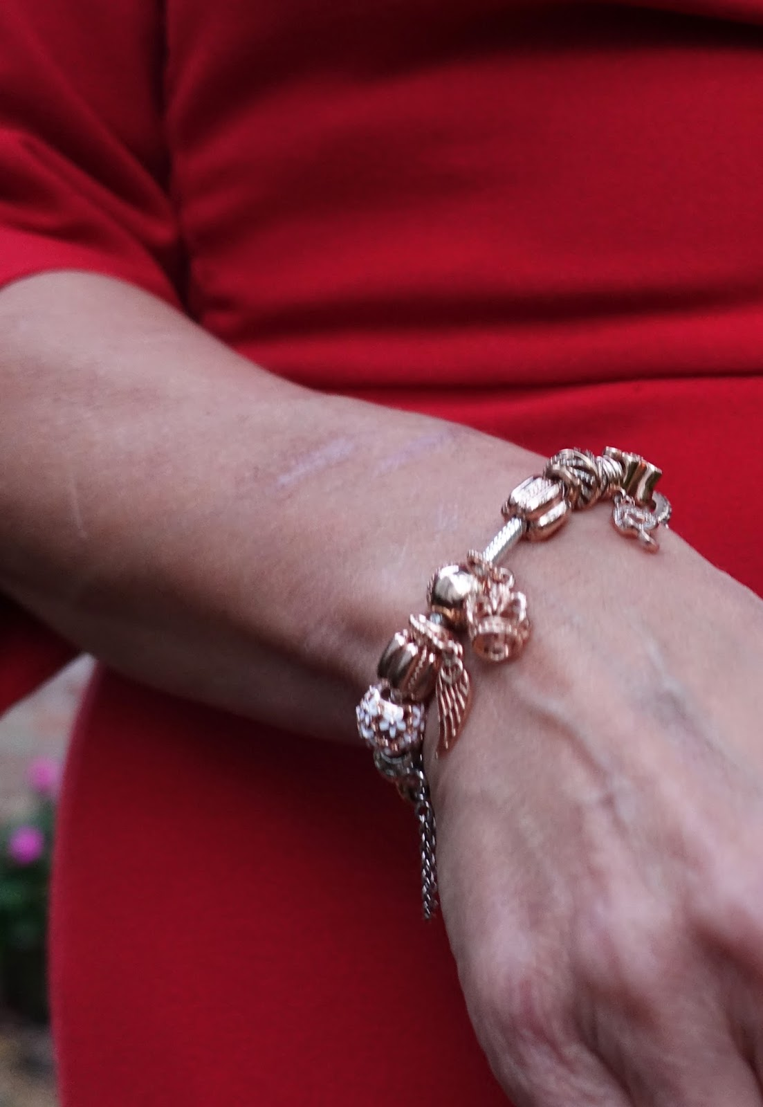 Image showing a close up of a woman wearing a Pandora rose gold bracelet with charms