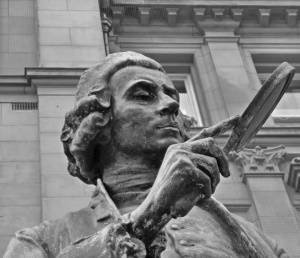 A imagem mostra uma estátua com uma lupa.