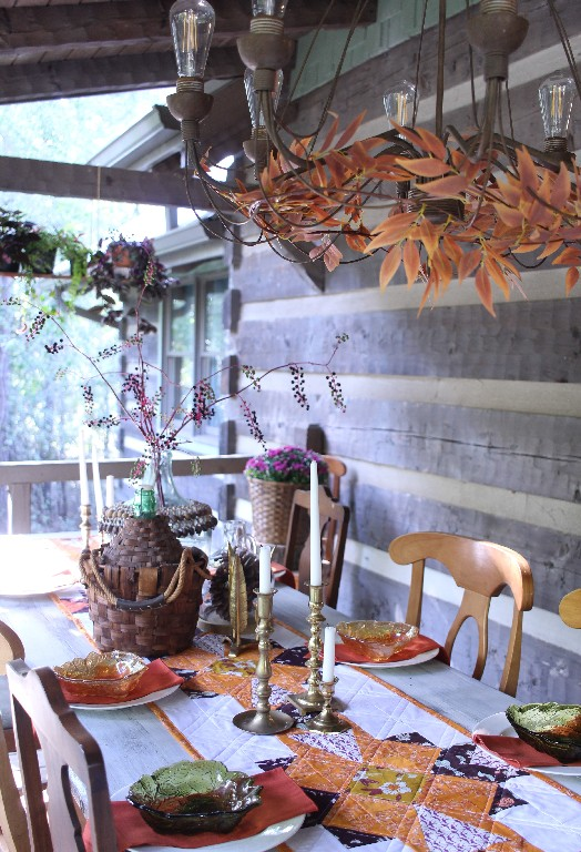 A Fall tablesetting on a rustic porch, with a quilted table runner in orange and purple, vintage green and amber glass dishes, and brass accents