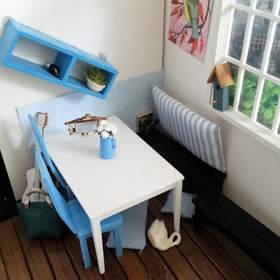 View of a one-twelfth scale modern miniature cafe scene, in blue and white with a bird theme. A display shelf has fallen off the wall, with the contents having knocked over several other components of the scene, and edned up on the floor.