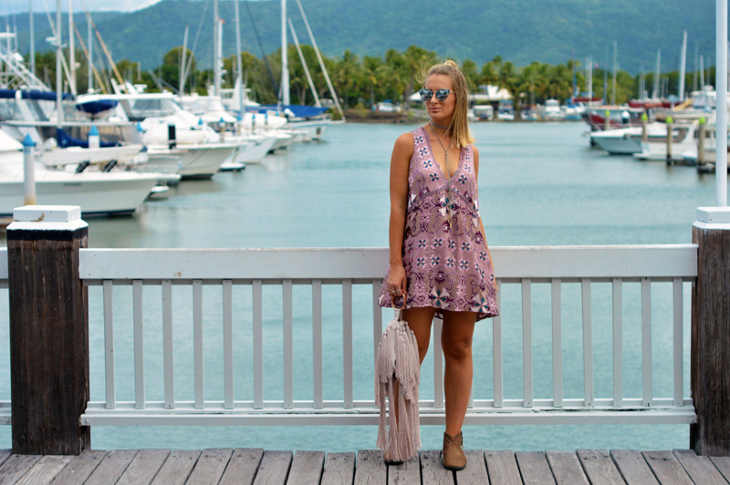 blonde fashion blogger wearing mauve boho floral print dress fringe bag beige ankle boots