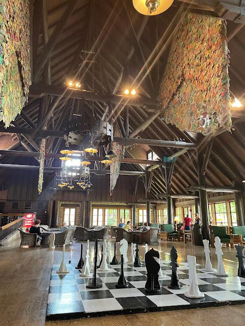 color photo of main room, log beams, lifesize chess set Pere Marquette lodge Grafton Illinois
