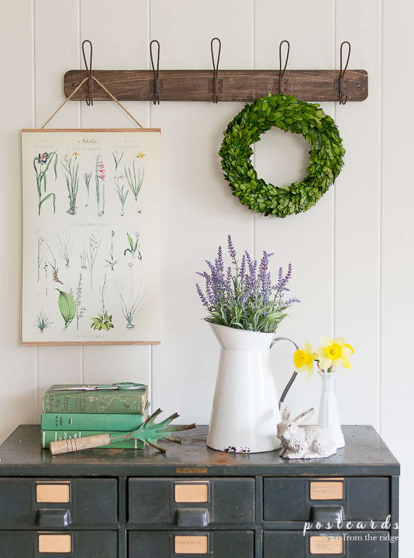 spring decor including faux flowers, boxwood wreath, and botanical art