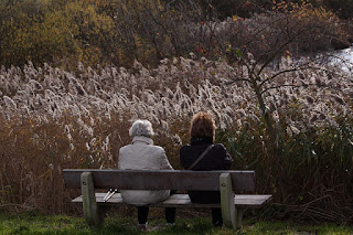 two women sitting on a bench, one older than the other.