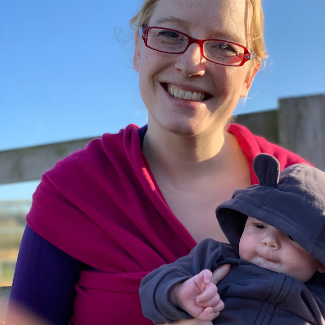 Mum wearing stretchy wrap and holding baby in hoody