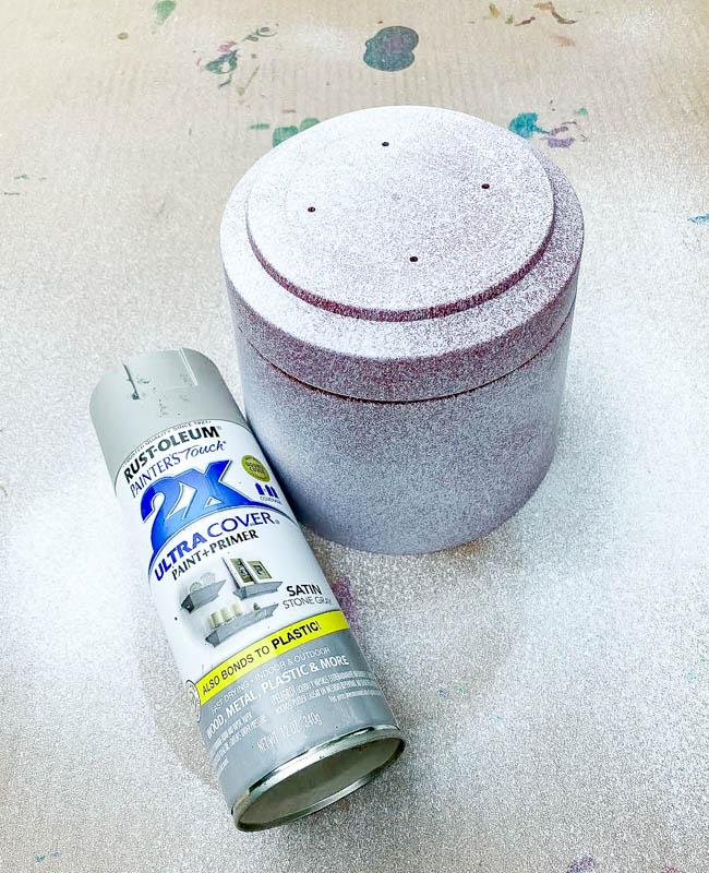 Spray painting planter with light gray spray paint