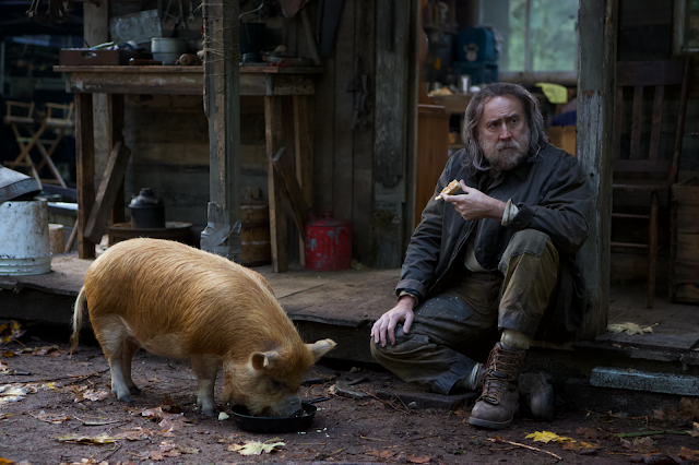 A bearded man sits next to his pig on a porch