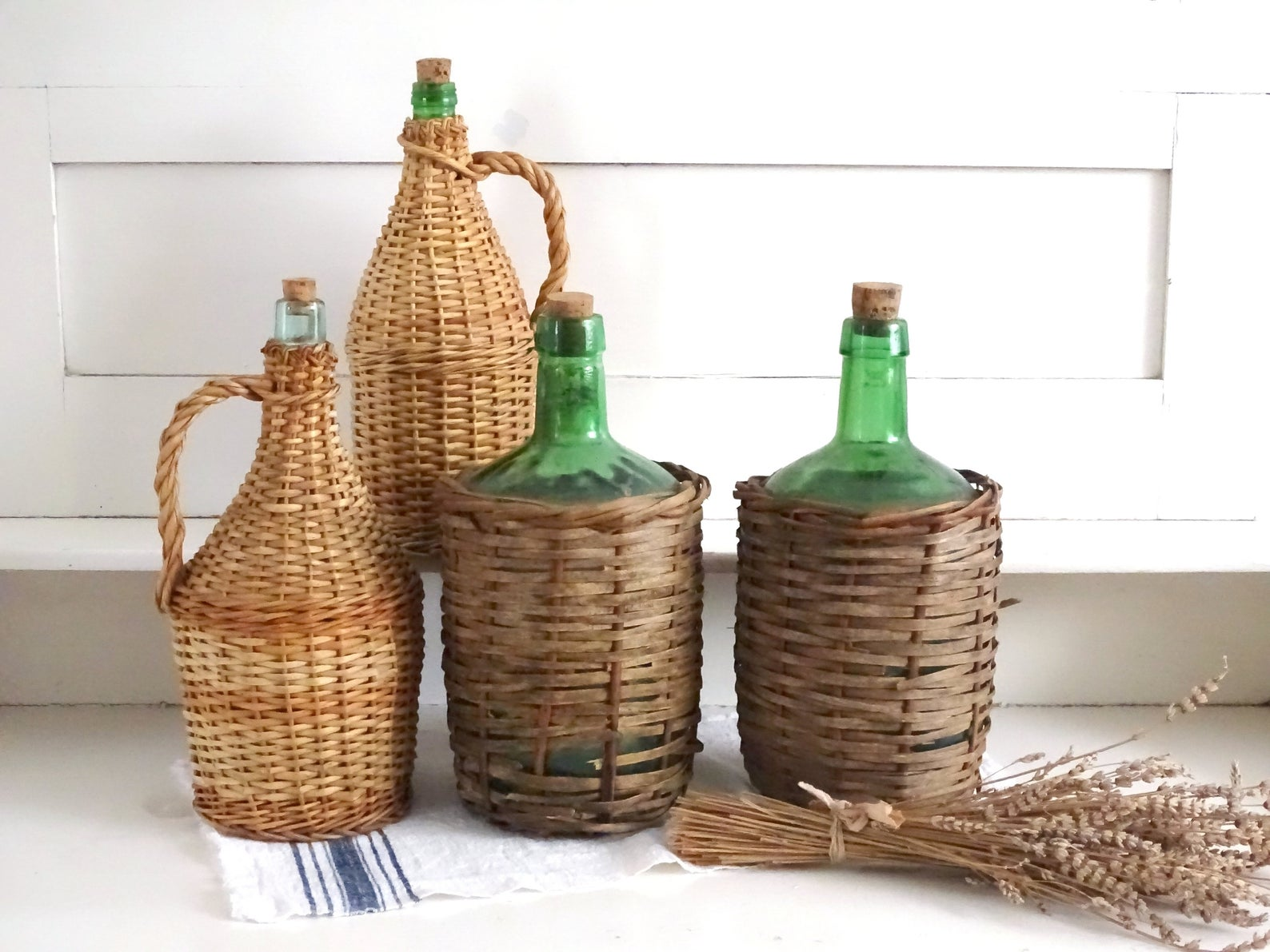 A collection of wicker wrapped demijohns