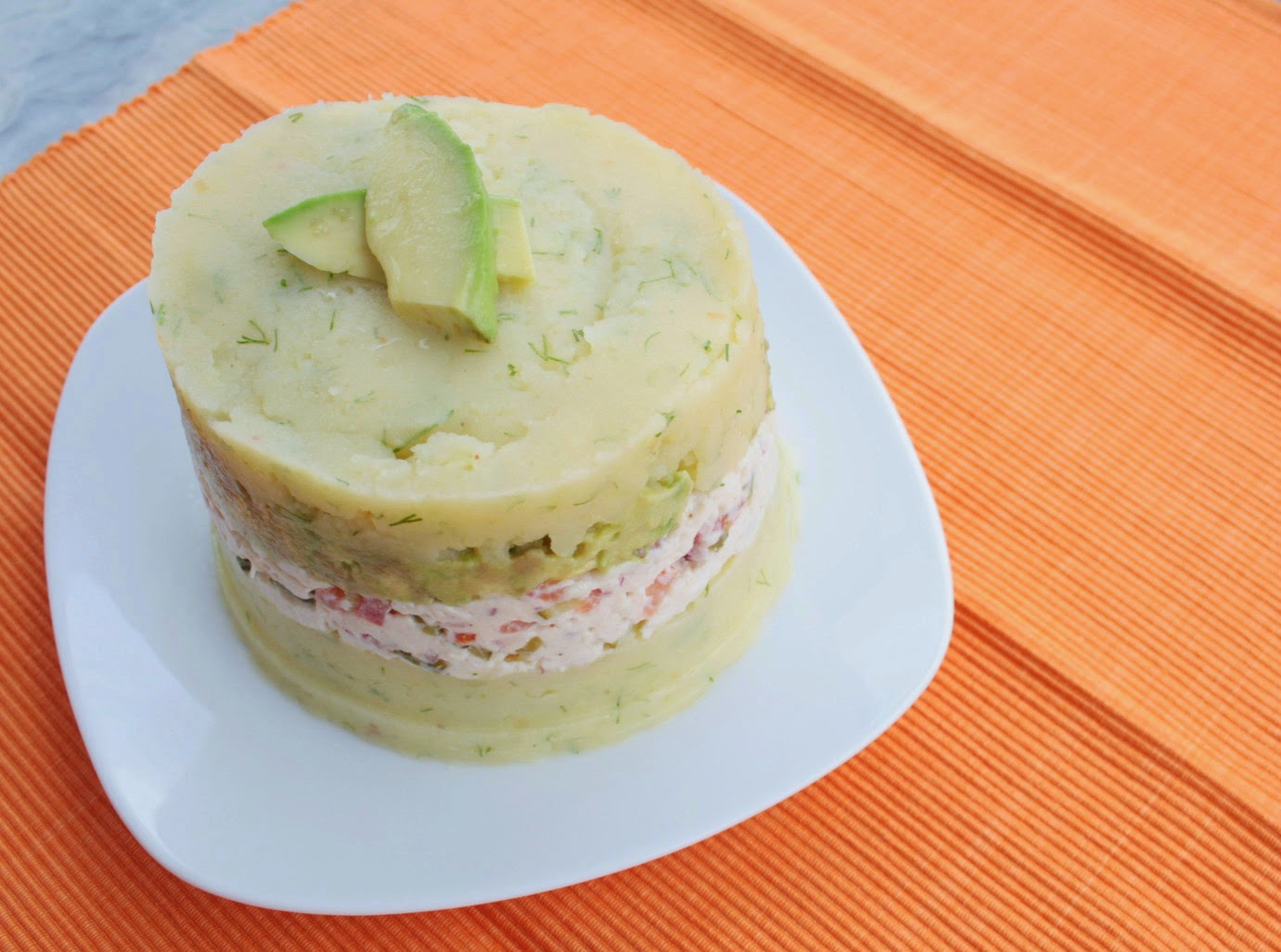 Chicken & avocado causa - a twist on the classic Peruvian chilled potato and chicken salad.  Lime and dill add a fresh taste to the mash which is complimented by the cornichon, red onion and tomato in the chicken salad.