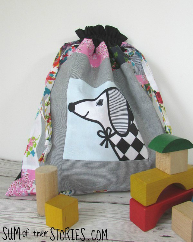 Learn how to make a patchwork drawstring bag with fussy cutting and scrap fabric. Tutorial by Sum of their Stories
