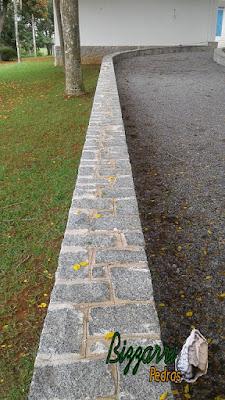 Revestimento com pedra folhetinha de paralelepípedo e a capa das muretas com pedra paralelepípedo rachado saindo 5 cm para fora do revestimento com o piso com pedrisco em sede de fazenda em Atibaia-SP.