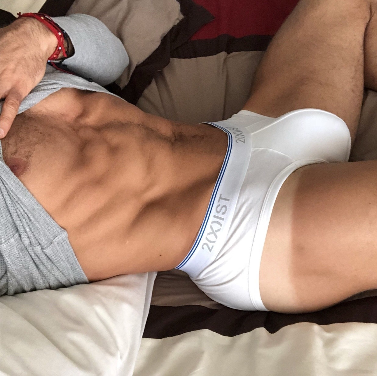 Scotty is lying on his bed in a pair of white briefs rubbing his huge cock through the fabric