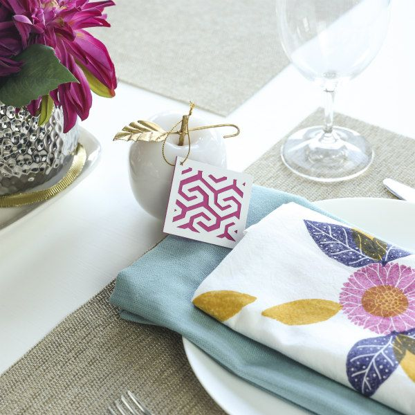paper cut tag and fabric printed napkin in a table place setting