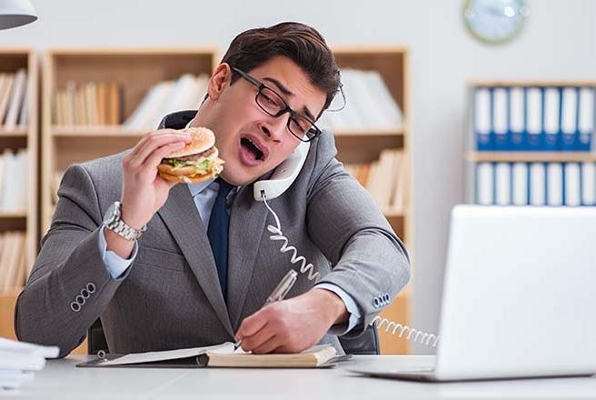 pemuda makan di meja kerja