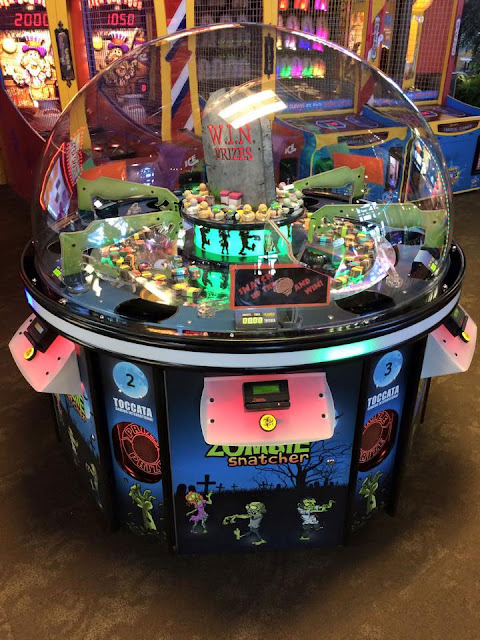 Big glass dome, inside are four zombie arms that can be controlled with their own switch to knock prizes into a chute.