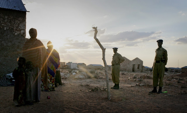 A woman and her young children stand in the evening light at an Internally Displaced People settlement in South Galkayo, Somalia with armed police standing guard.