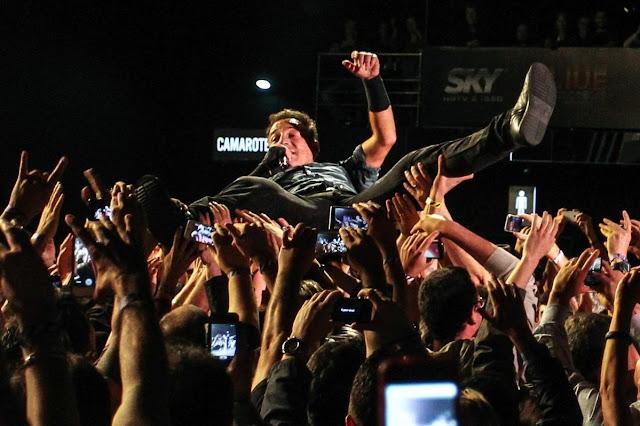 """Elvis e sua geração já eram capazes de gerar frenesi nos salões, fossem recintos de high school, espaços tradicionais como o Madison Square Garden ou shows de tevê coast to coast, como o de Eddie Sullivan. Os Beatles formataram a histeria descabelada (embora o empresário Brian Epstein tenha pago carpideiras profissionais para a cena do aeroporto na """"docuficção"""" A Hard Day's Night). O rock ainda não havia extrapolado para os descampados da natureza, na simbiose promíscua de lama, sexo, bebida, marijuana, protesto, delírio, orgia, chuva e banheiro químico. Ali, nos festivais ao vivo, a geração dos anos 60 encontrou sua particular ideia de felicidade.   Nas manifestações coletivas do que se passou a chamar paz e amor,  uma contracultura florescente e psicodélica adotou o rock como sua língua franca. O poeta beat Gary Snyder flagrou o parto de """"uma nova ética e novos estados mentais"""". Ou como dizia Jerry Garcia, emblemático band leader do emblemático Greatful Dead, """"somos os primitivos de uma cultura desconhecida""""."""