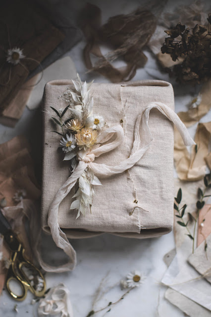 neutral linen furoshiki wrapping with handmade flower topper
