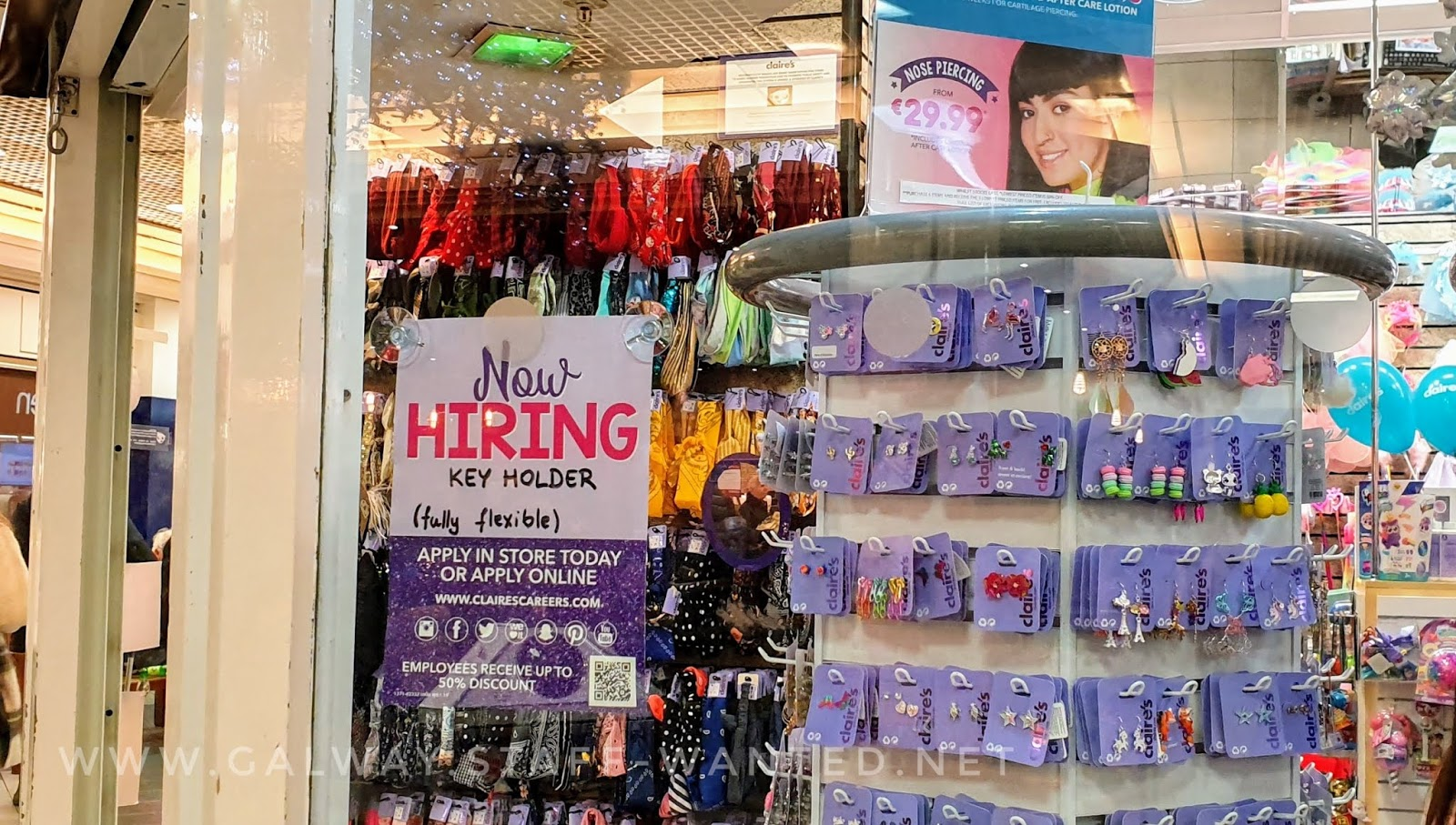 shop widow showign wanted sign - and a rotating earring display with pairs of Claire's own-brand earrings, including Christmas-earrings, displayed on light purple card