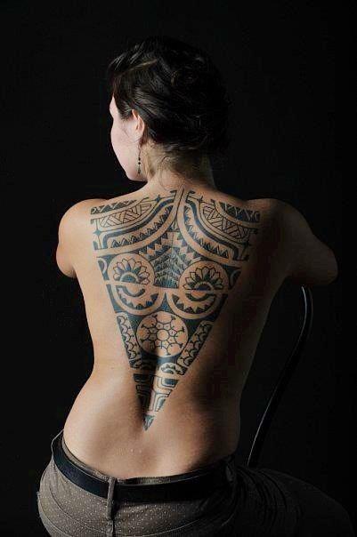 Vemos a una mujer sentada, en su espalda luce un precioso tatuaje maori