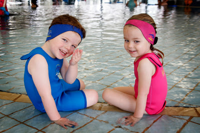 Image of 2 children sitting on the edge of the pool wearing headbands to help hold in their ear plugs.