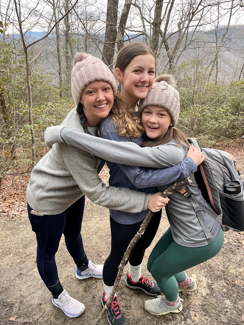 mom and 2 teen girls hugging on a hike