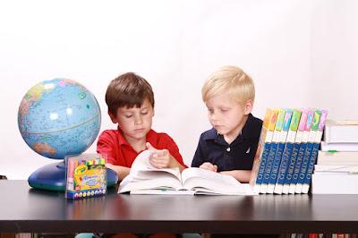 Chicos estudiando con sus libros, marcadores y globo terráqueo