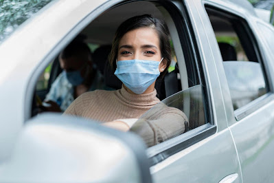 A woman wearing a face masks sits in the driver's seat of a car, smiling and looking out the window.