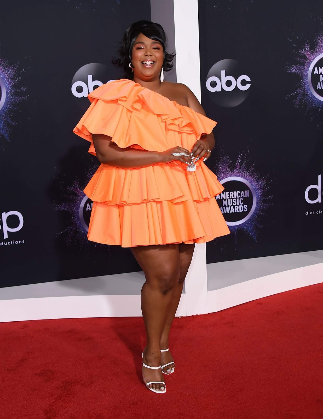 Lizzo rocked the red carpet in a ruffled, orange minidress and a very miniature purse