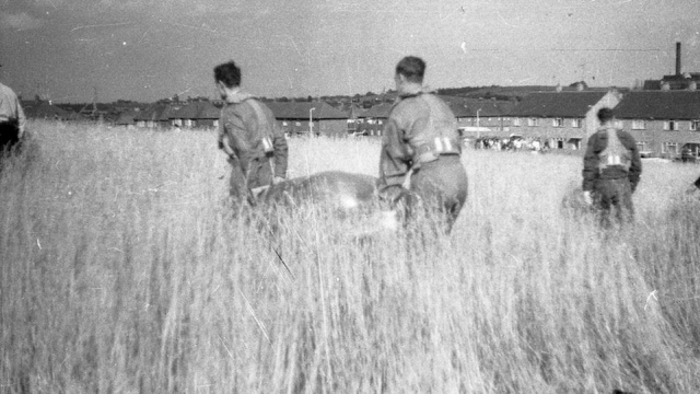 Military personnel recovering from a farmers field a silver Flying Saucer.