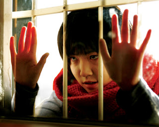Girl looking through barred window