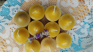 a set of beeswax candles with small purple flower