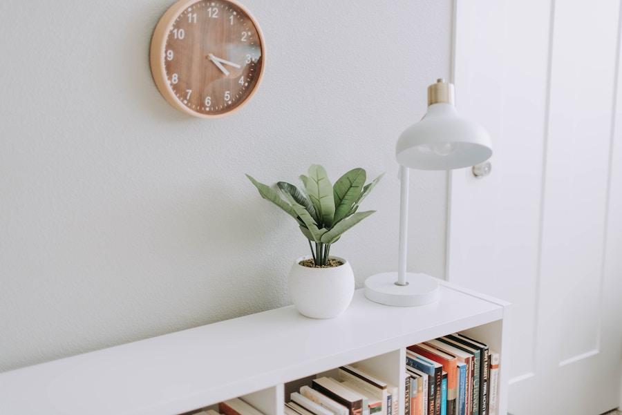 estantería baja con lámpara, planta y reloj