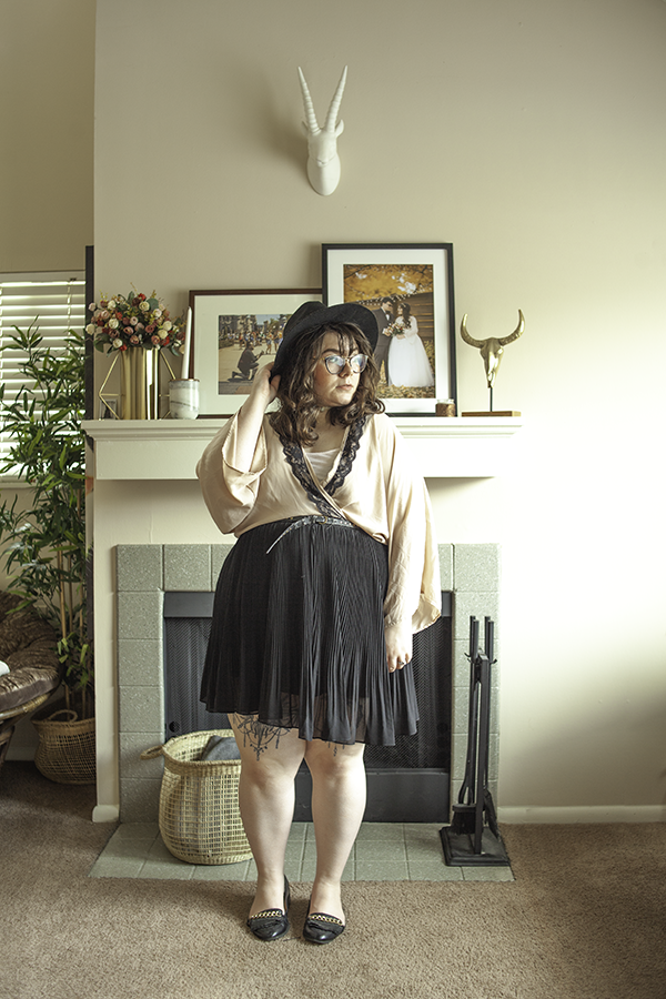 An outfit consisting of black wide brim fedora, a pastel pink with black lace trim kimono style cardigan crossed and tucked into a black pleated mini skirt with black loafers.