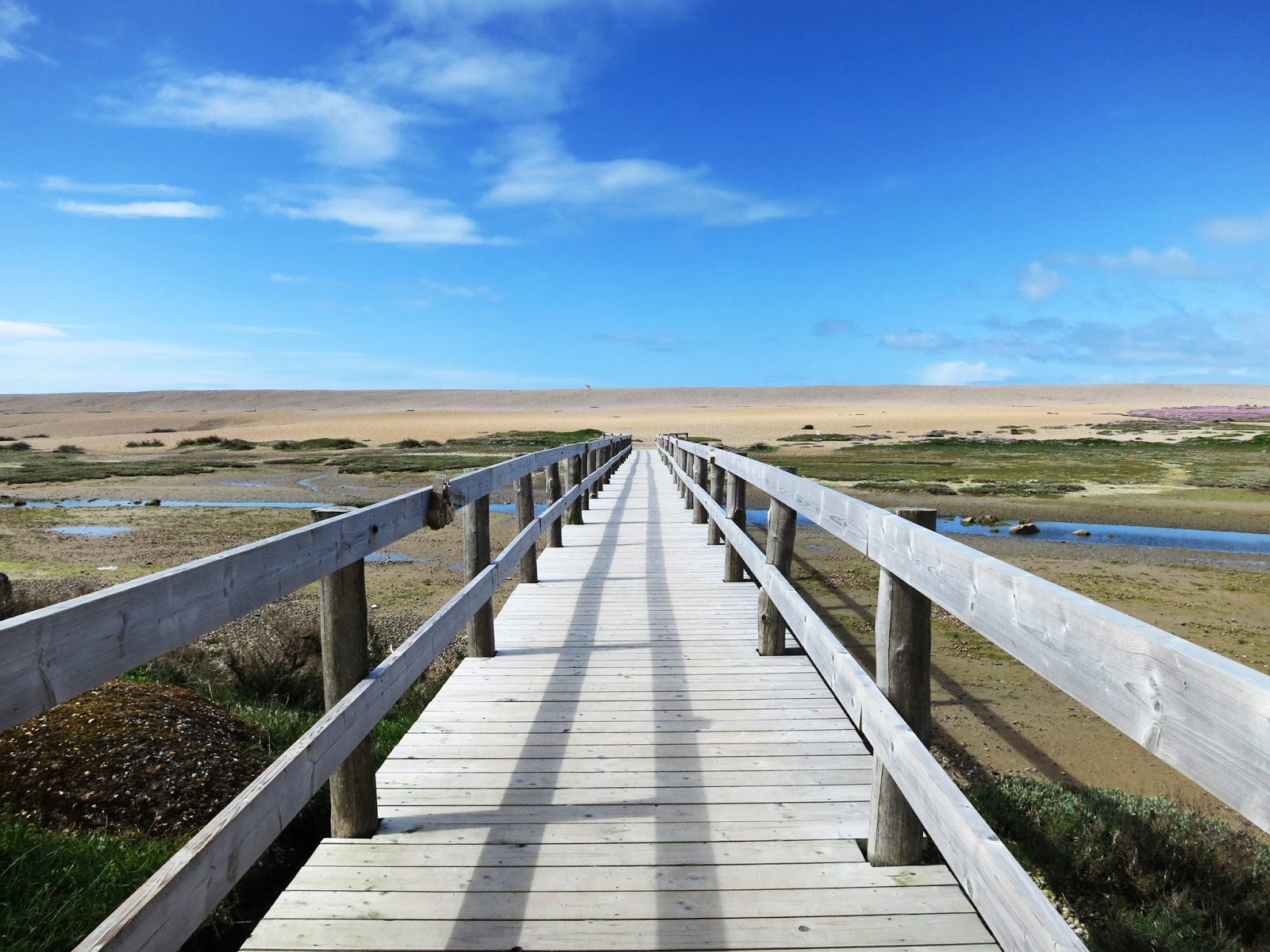 Wooden bridge with shadows leading to Chesil Beach across Fleet with tide out