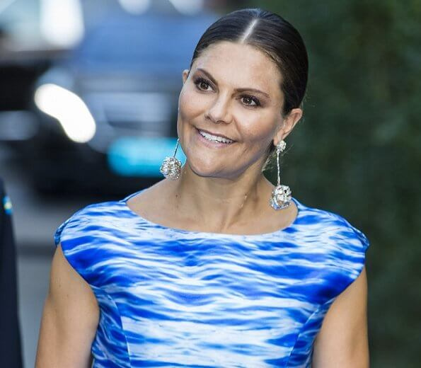 Crown Princess Victoria wore a Camilla Thulin sea blue print dress and carries Anya Hindmarch metallic clutch