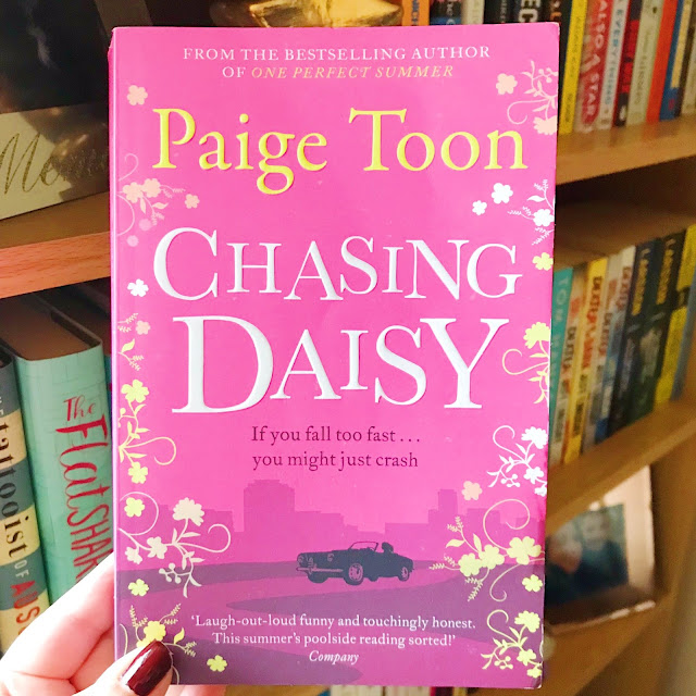 Chasing Daisy by Paige Toon held up in front of bookshelf