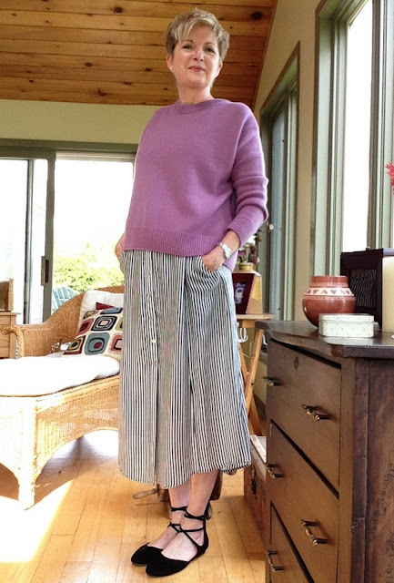 woman in striped mid-skirt, pink sweater, and black flats, with her hands in her pockets