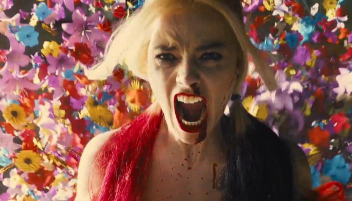 Imagem: a Arlequina, interpretada por Margot Robbie, com os cabelos longos dividos e com mechas vermelhas e pretas, em um vestido vermelho, gritando, com o nariz sangrando e dezenas de flores explodindo às suas costas.