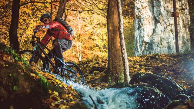 Man riding bike over creek