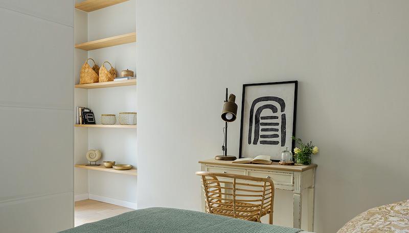 Mesa rústica de estudio y librerías de madera a media en retranqueo de la pared de un dormitorio rústico/moderno
