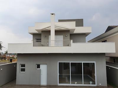 Na elevação posterior, a chaminé da churrasqueira inserida na cozinha do pavimento térreo, atua como pilar de sustentação do pergolado sobre o terraço da suíte do casal, no pavimento superior.